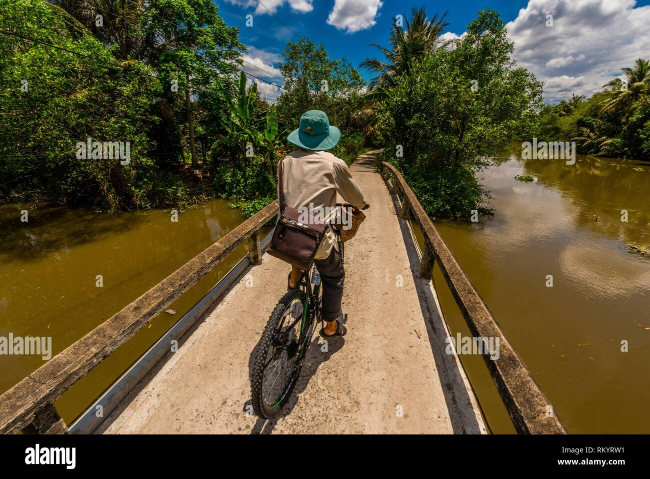 A man bicycling along the backwaters, Cai Lay, Mekong Delta, Vietnam. - Stock Image