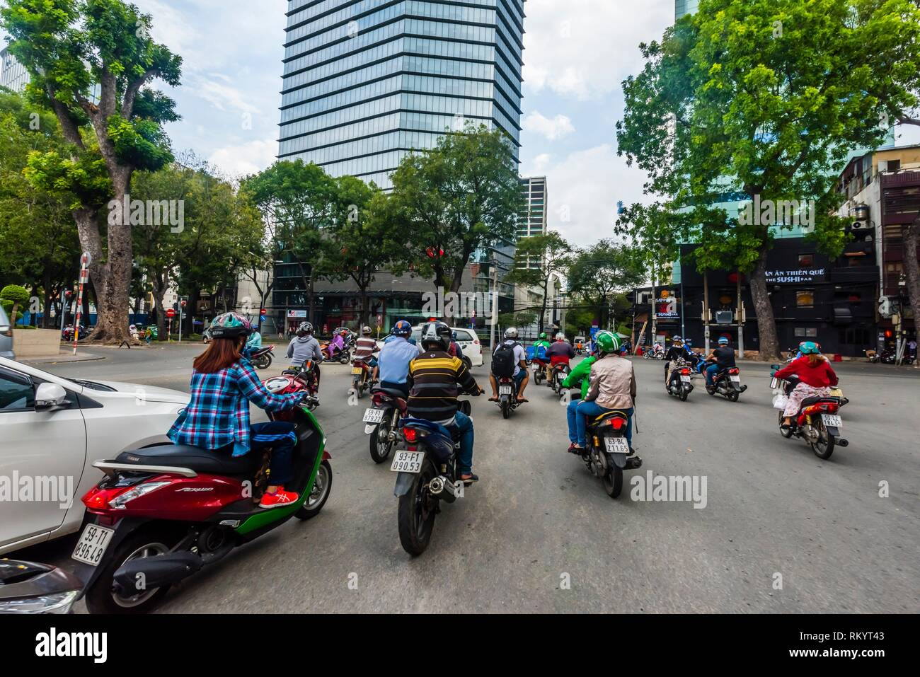 Grab driver (motorcycle taxi), Two-wheeled traffic in Ho Chi Minh City (Saigon), Vietnam. There are over four million motorbikes in the city. - Stock Image
