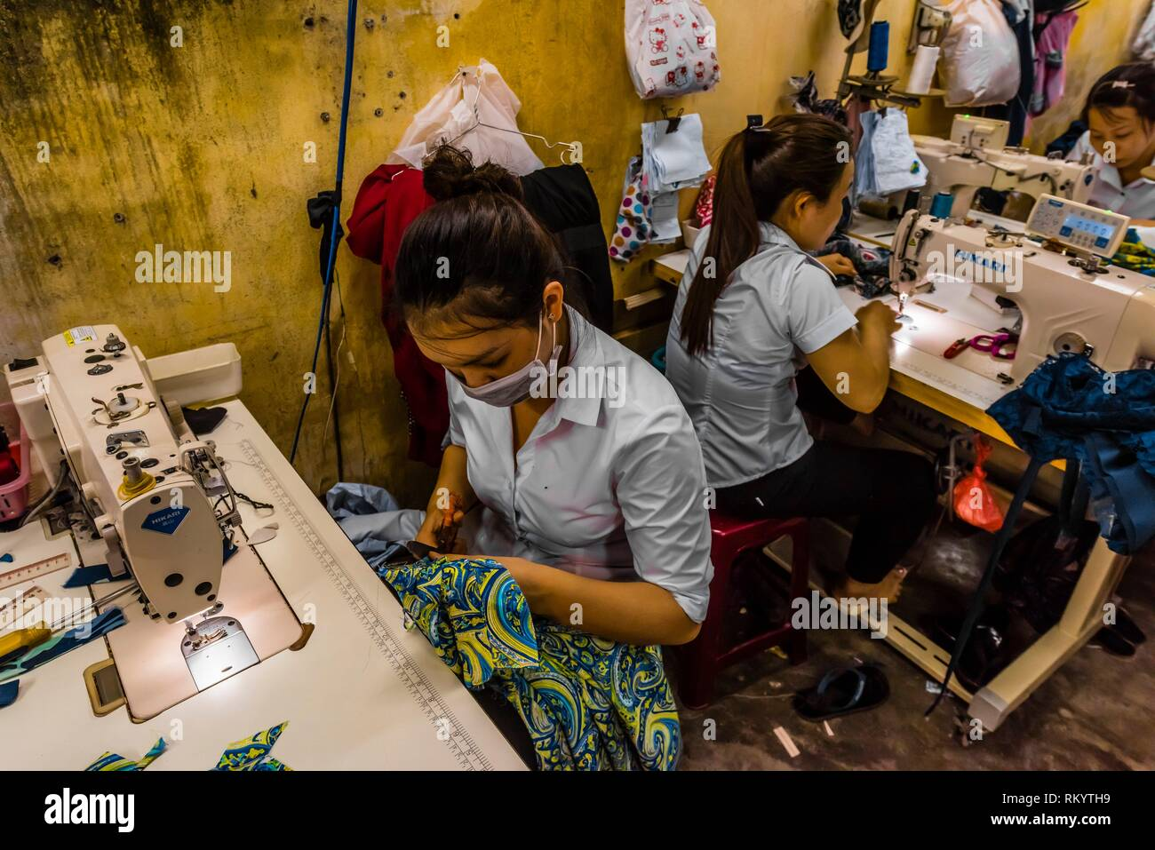 Tailors at work on garments, Yaly Couture, the most prestigious bespoke tailor and shoemaker in Hoi An, Vietnam. - Stock Image