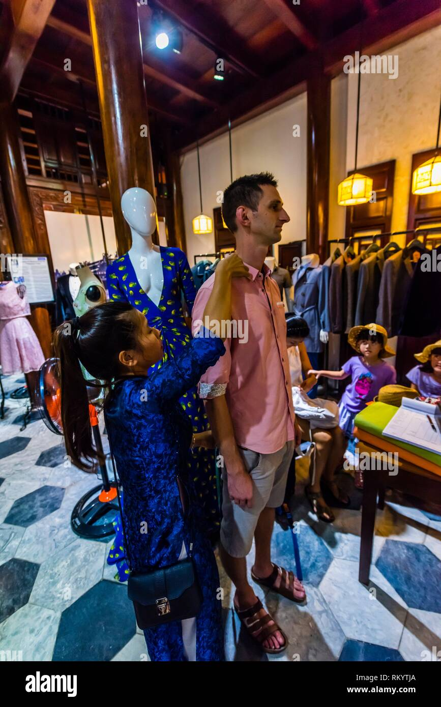 A customer getting first meaurements for a suit, Yaly Couture, the most prestigious bespoke tailor and shoemaker in Hoi An, Vietnam. - Stock Image