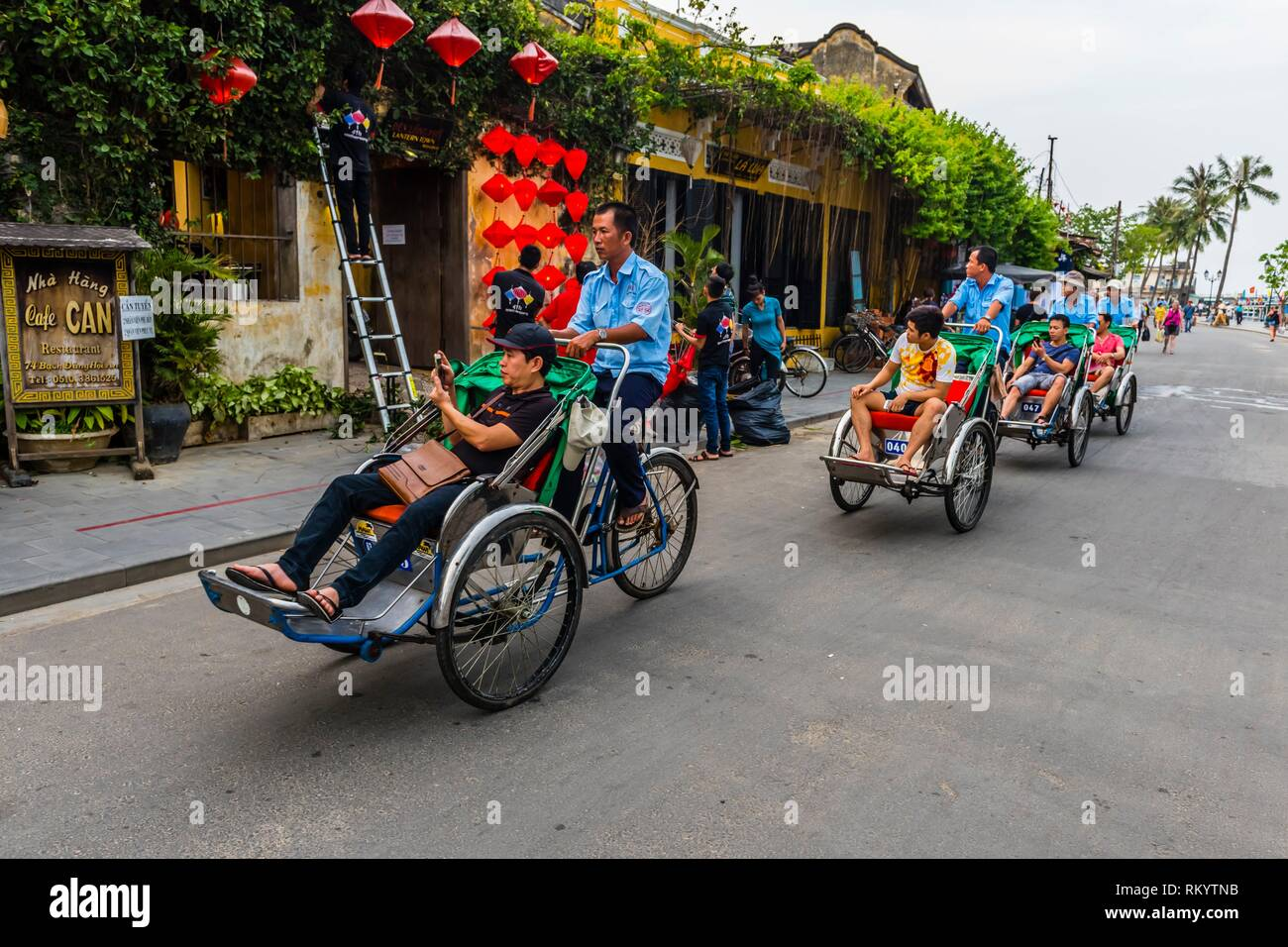 Tourists peddled through the Old Town on Cyclos (three wheeled bicycle taxis), Hoi An, Vietnam. - Stock Image