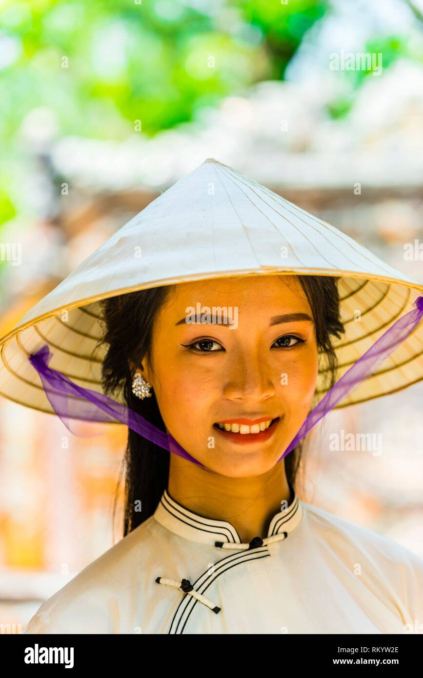 Vietnamese woman wearing the traditional ao dai costume in the Imperial City, a walled palace within the citadel of the city of Hu? which is the Stock Photo