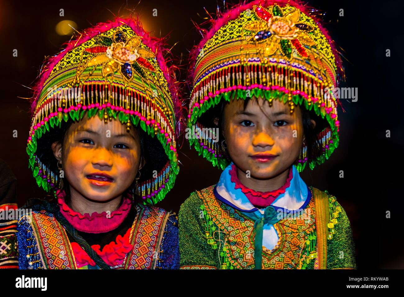 Flower Hmong (hill tribe) girls in traditional costume in Sapa, northern Vietnam. - Stock Image
