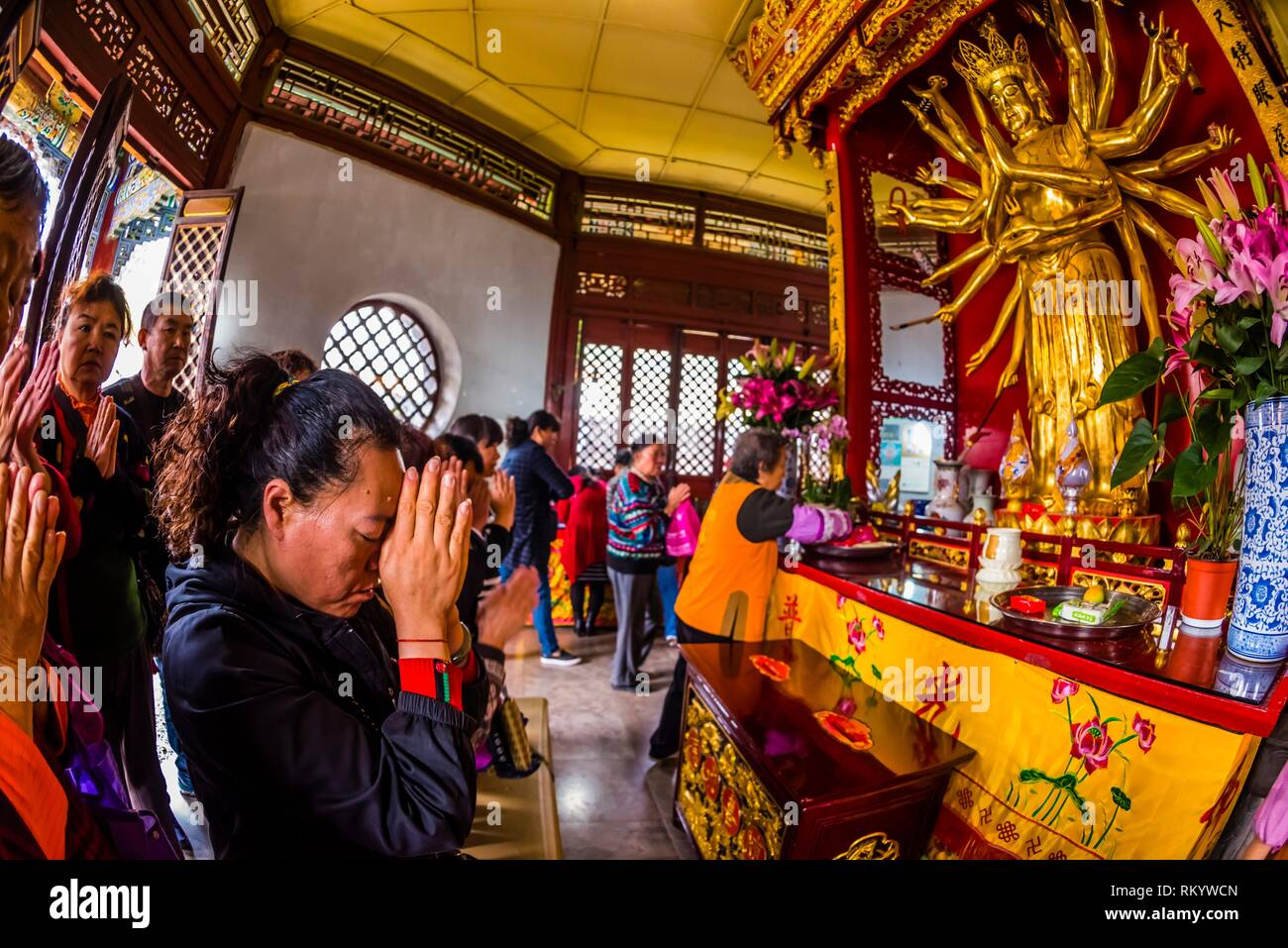 Buddhists praying to the statue of the Avalikitesvara Goddess, Yuantong Temple, the largest Buddhist temple in Kunming, Yunnan Province, China. It - Stock Image