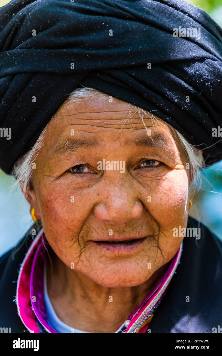 Woman of the Bai ethnic minority wearing a characterisitic tunic, Black Dragon Pool Park, Lijiang, Yunnan Province, China. - Stock Image