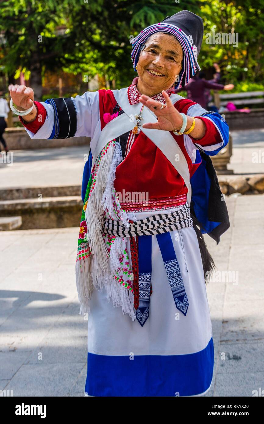 An elderly woman of the Naxi minority dances in a square in the Old Town (Dayan) of Lijiang, Yunnan Province, China. The Old Town is a UNESCO World - Stock Image