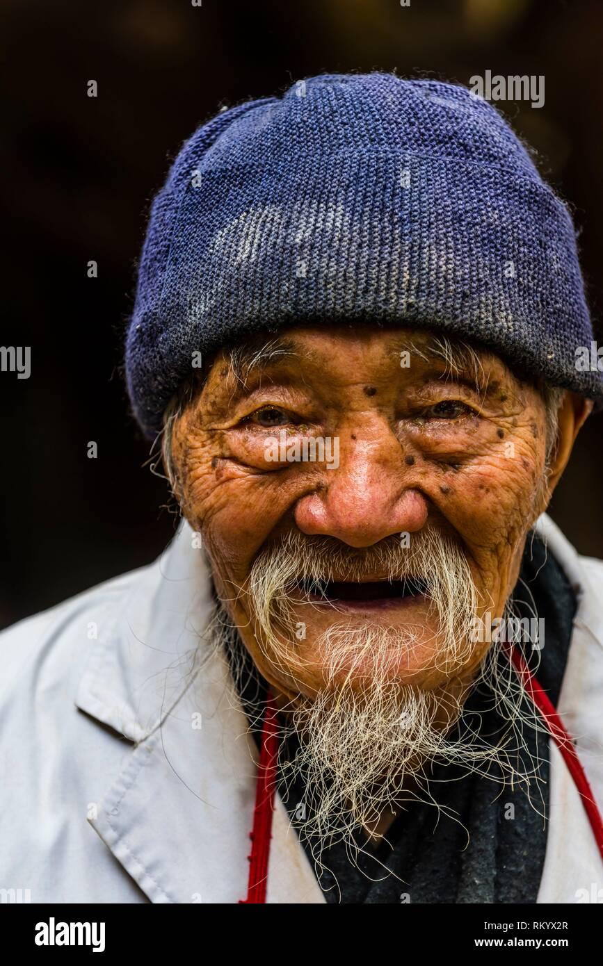 95 year old Dr. Ho Shixiu, a famous herbalist, at his Jade Dragon Snow Mountain Medical Clinic in the ancient village of Baisha; near Lijiang, Yunnan - Stock Image