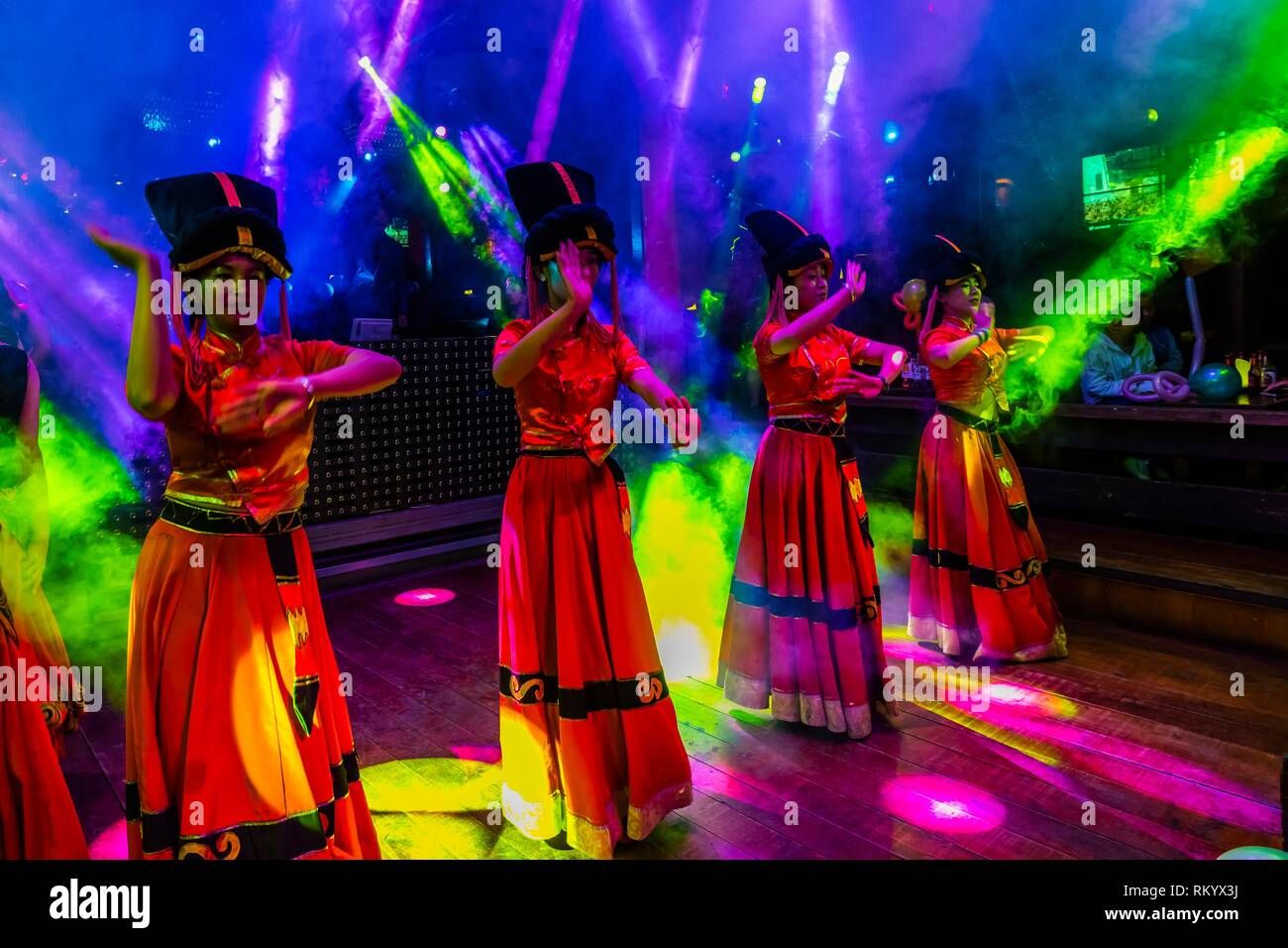 Dance performances in bars and night clubs along Bar Street (Xinhua Street) in the Old Town (Dayan) of Lijiang, Yunnan Province, China. - Stock Image