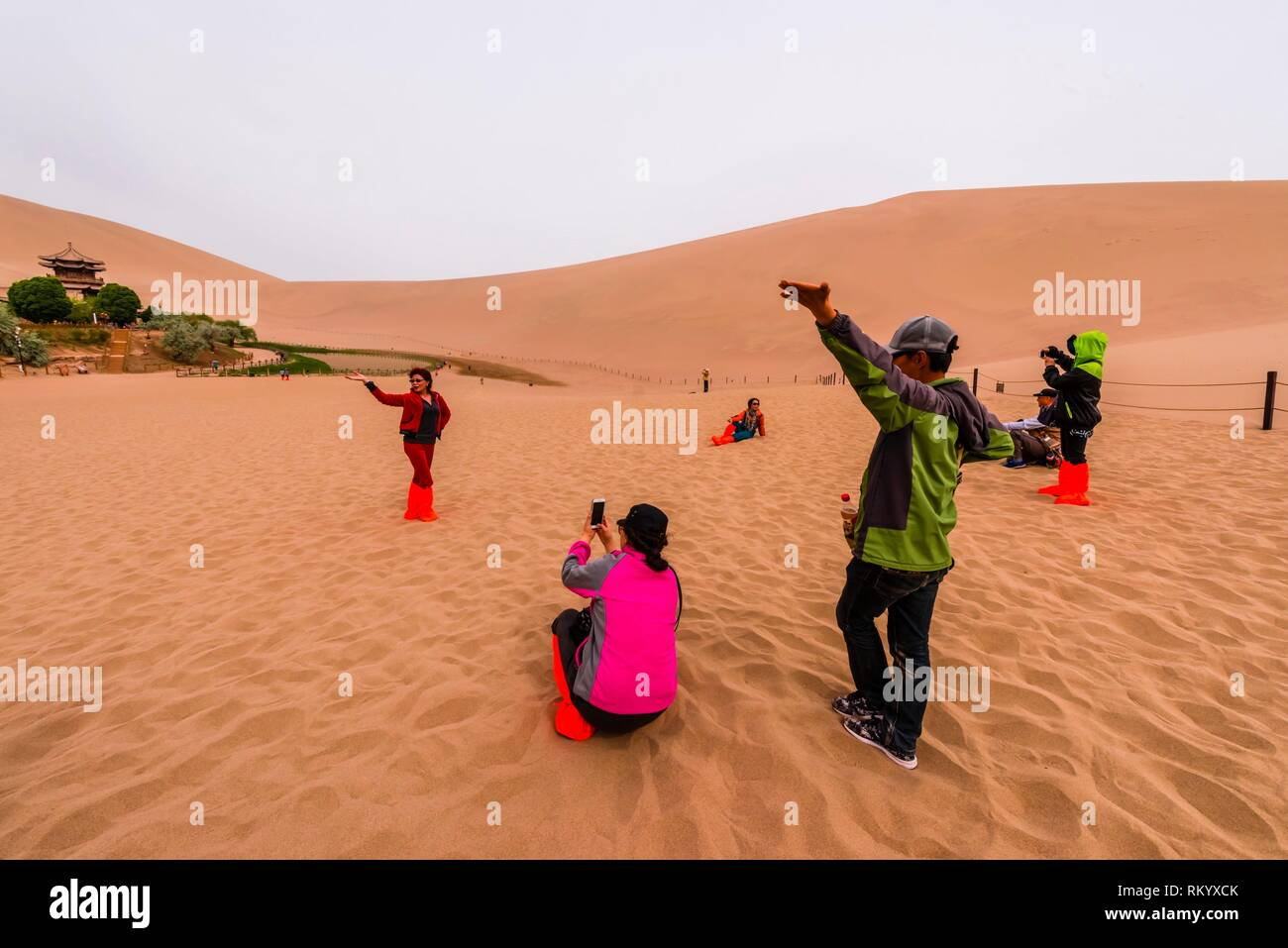 Chinese tourists taking photos in the sand at the oasis at Crescent Lake (Yueyaquan), 6 km south of the city of Dunhuang in Gansu Province, China. - Stock Image