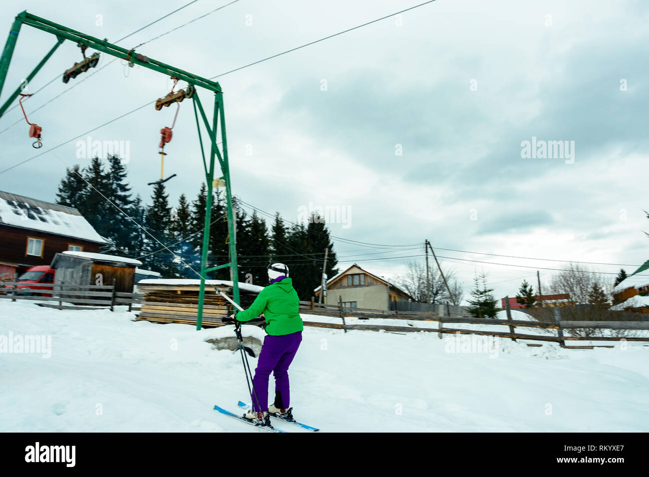 A skier silhouette in a ski suit and ski goggles slowly moving uphill on an anchor ski lift leaving traces in the snow on a cloudy blue sky background - Stock Image