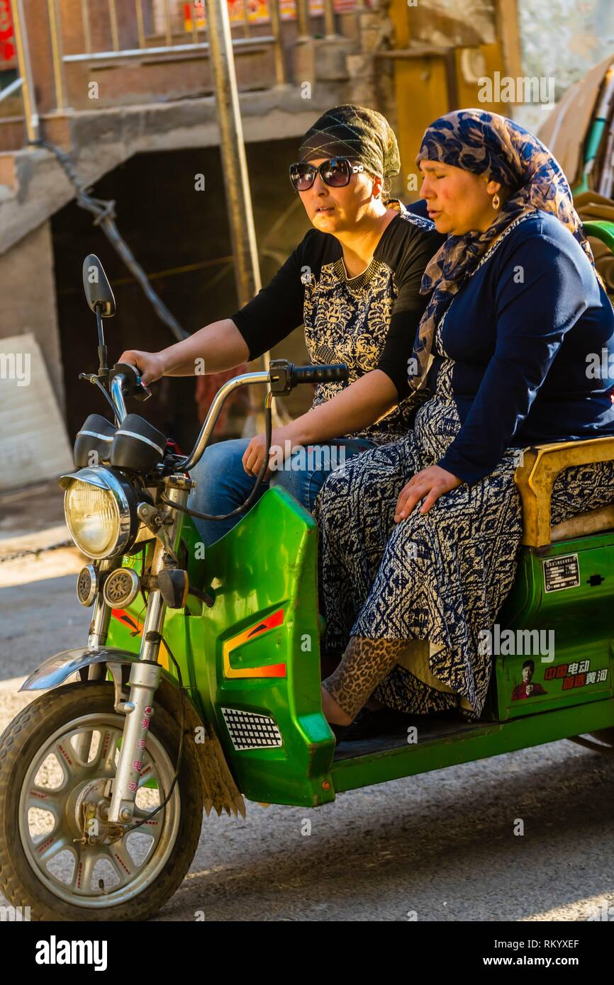 Three wheeled vehicles, Turpan, Xinjiang Province, China. Turpan is a small oasis town and former Silk Road outpost. Uyghur people are a Central - Stock Image