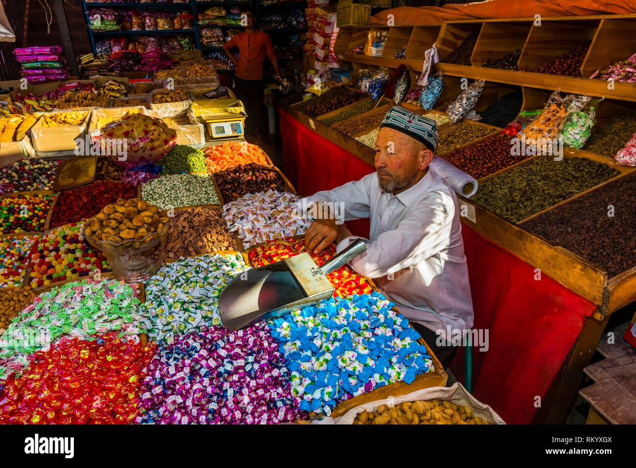 A shopkeeper selling sweets, nuts and dried fruit. Kashgar is an oasis city in Xinjiang Province, China. It is the westernmost city in China, located - Stock Image