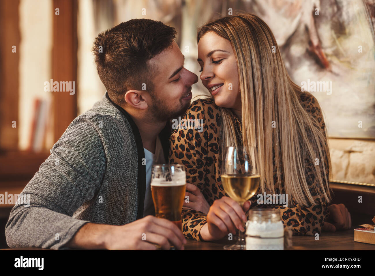 Romantic loving couple drinking beer, having a date in the cafe. - Stock Image