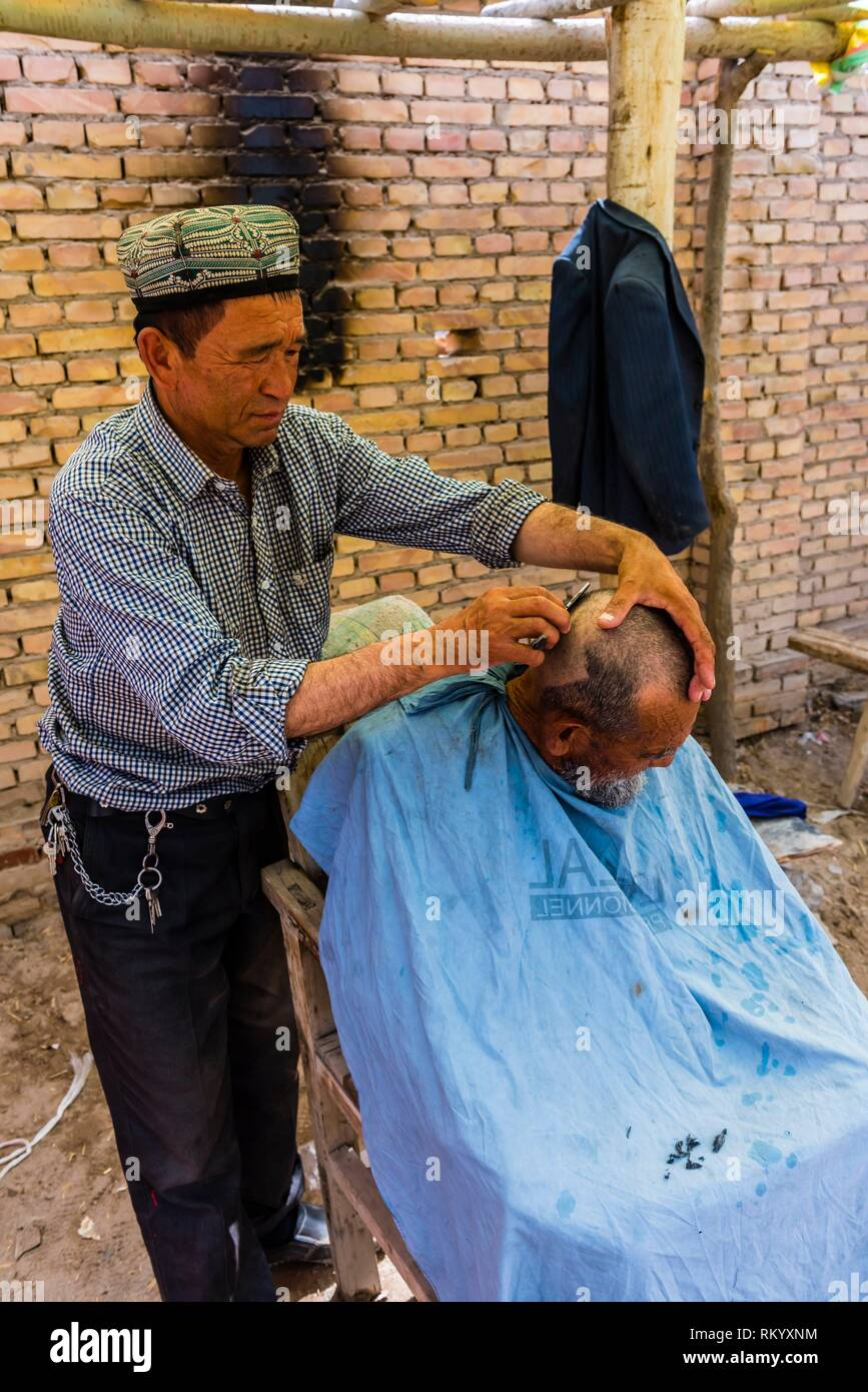 Uyghur man getting a haircut on the street at the weekly market at Opal (Upal), a village along the Karokoram Highway (50 km. southwest of Kashgar) - Stock Image
