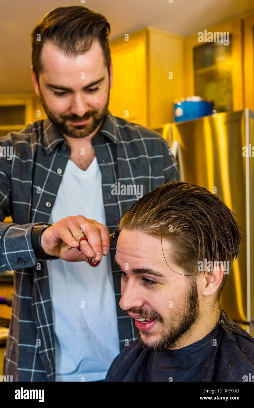 A 24 year old man having an extreme haircut, including cutting off a long ponytail for charity. Littleton, Colorado USA. - Stock Image