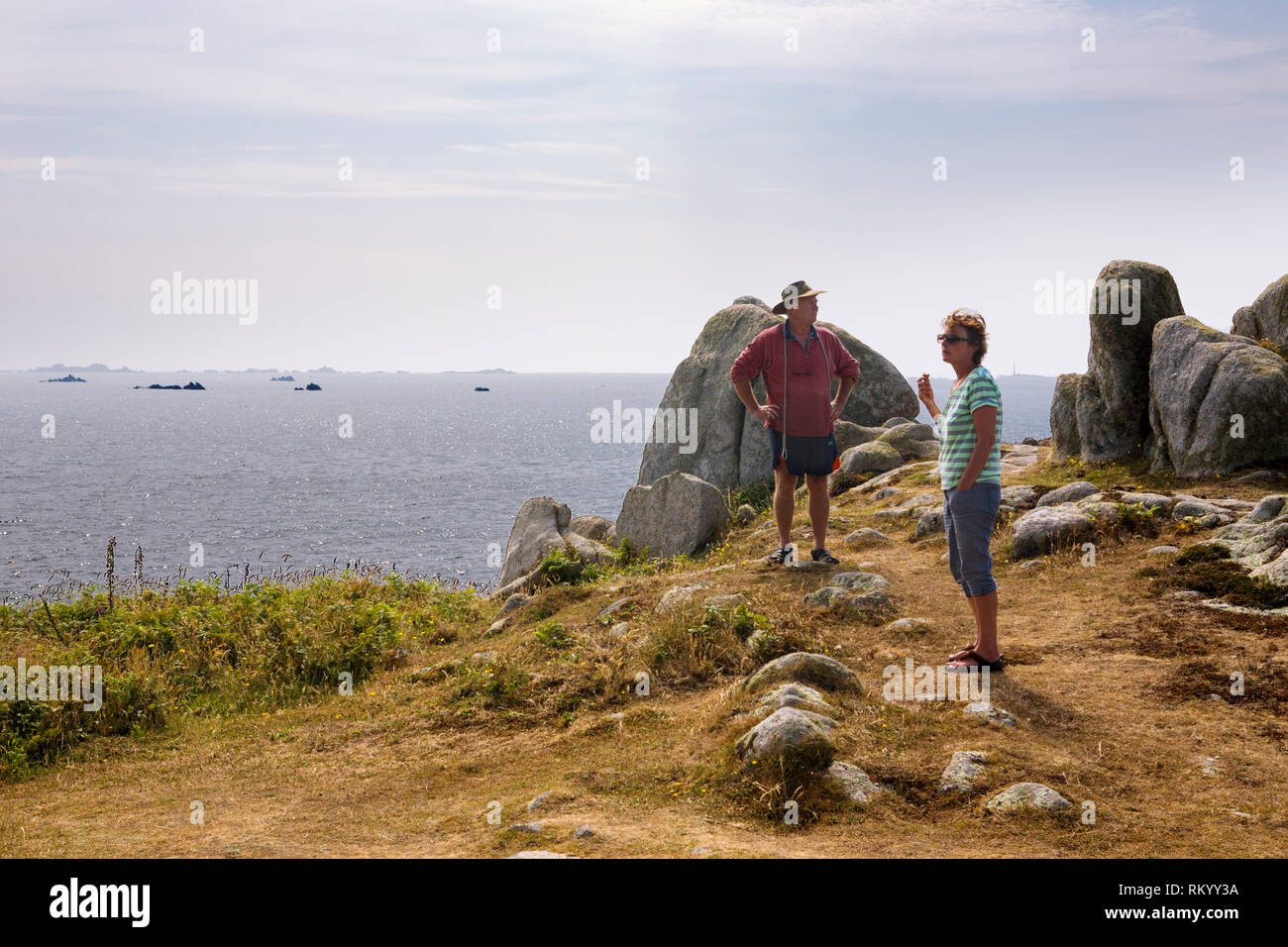Middle-aged hiking couple enjoy the view from Carnew Point, St. Agnes, Isles of Scilly, UK - Stock Image