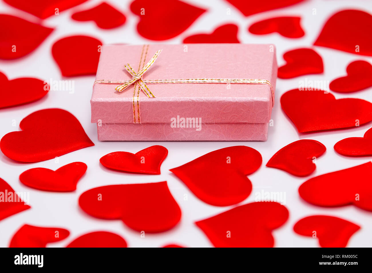 Top View of a Pink Gift Box Surrounded by Scattered Hearts on White Background. St. Valentines Day Concept - Stock Image