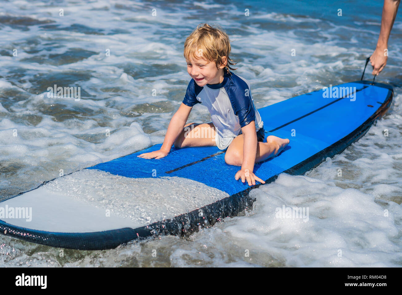 405c1cb39b Happy baby boy - young surfer ride on surfboard with fun on sea waves.  Active