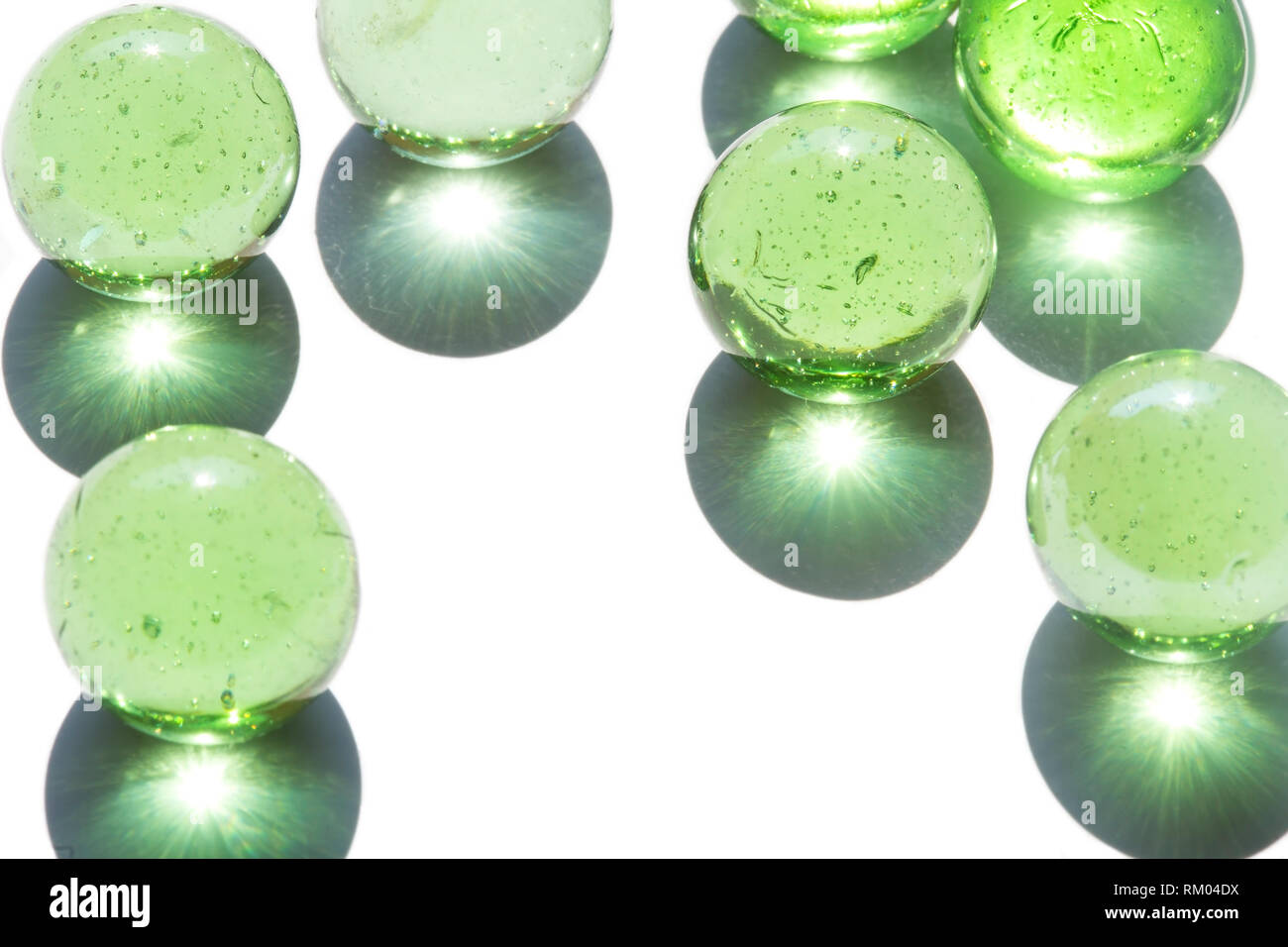 Green glass marbles with shadows - Stock Image