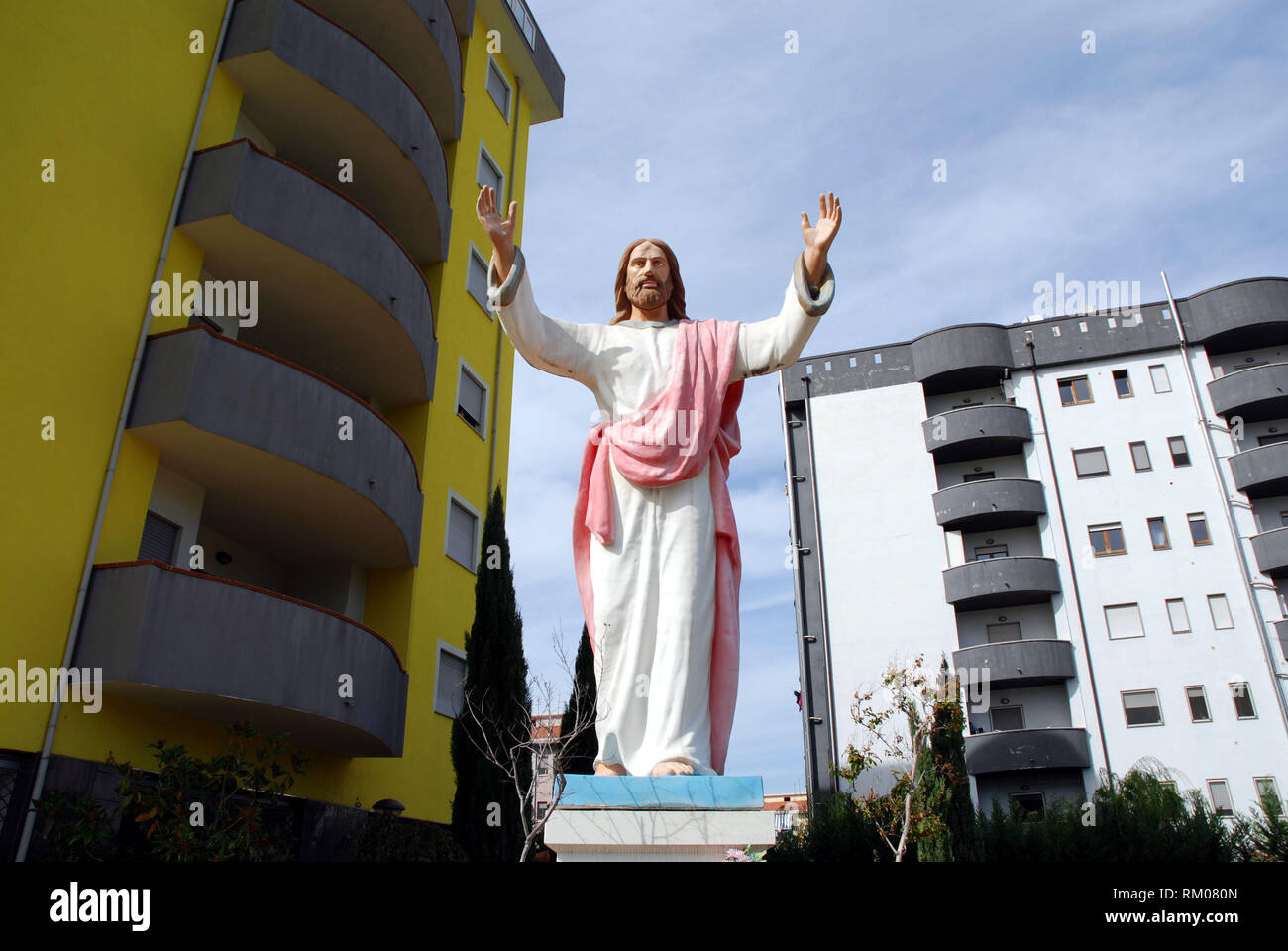 big and impressive statue of christ placed at the entrance of a residential complex as an ostentatious symbol of faith - Stock Image