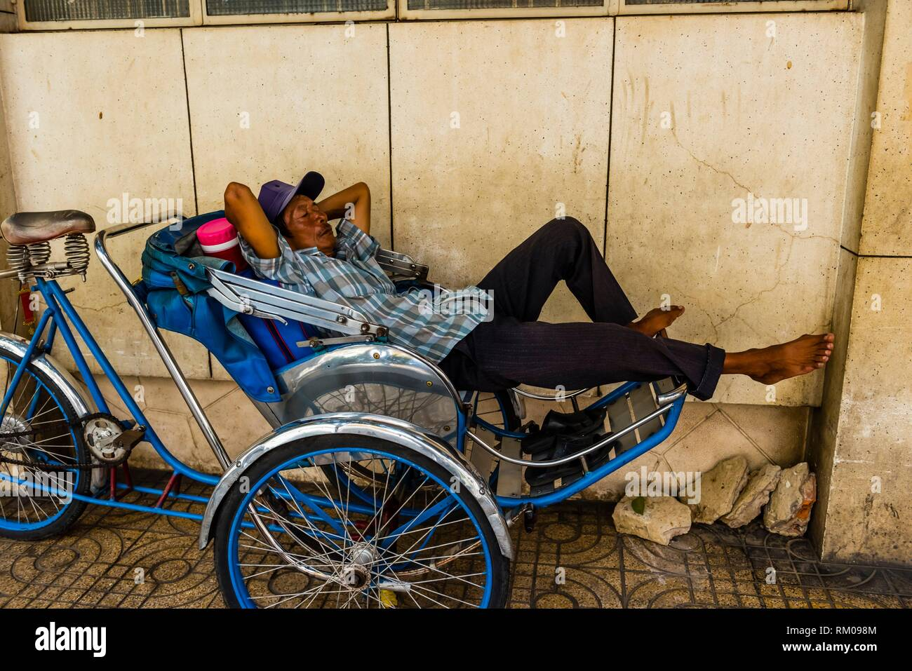 Man taking a nap on a cyclo (a three-wheel bicycle taxi), Ho Chi Minh City (Saigon), Vietnam. - Stock Image