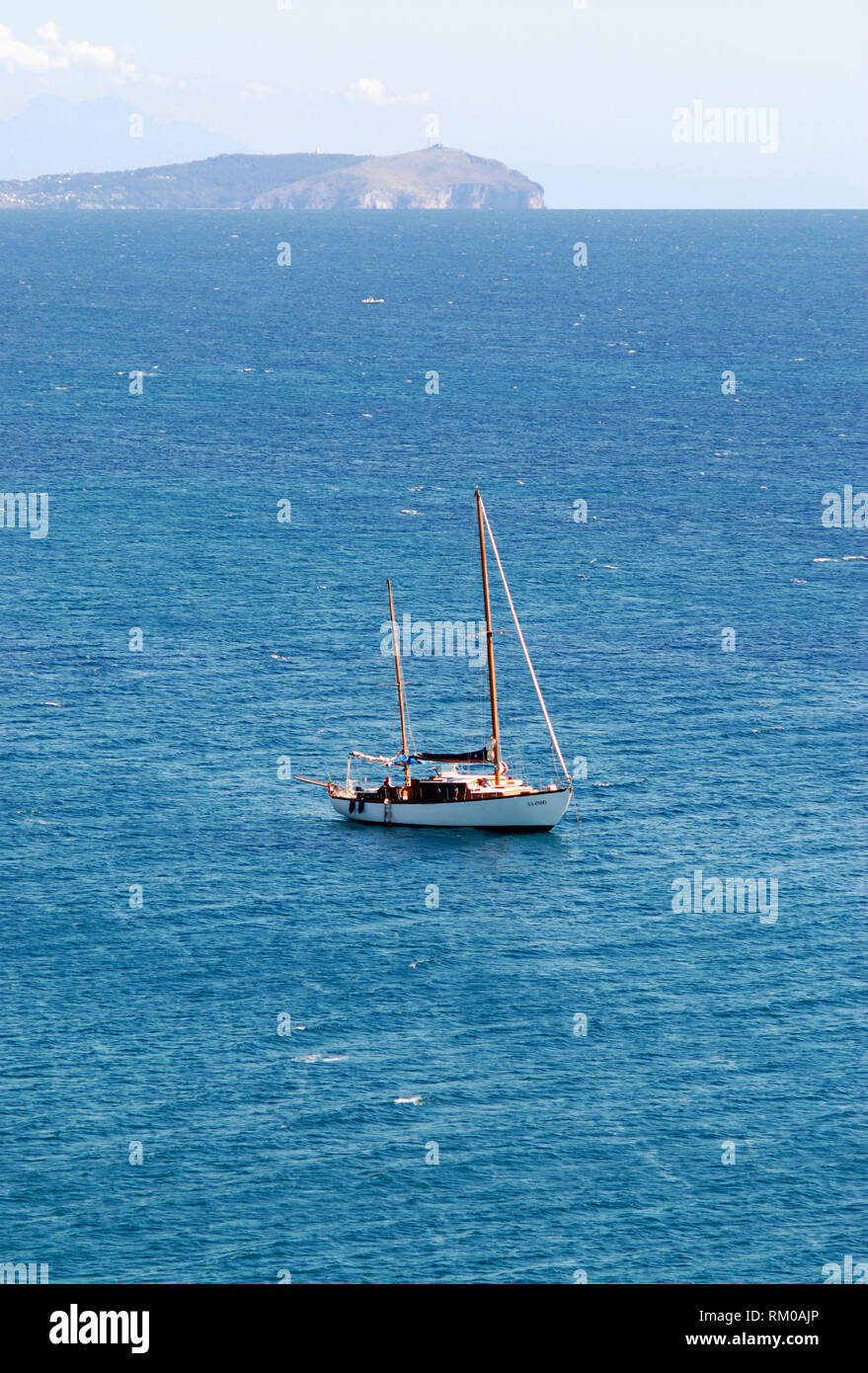 twin-shaft sail boat yacht enjoy the sea stopping quiet at anchor in the middle of the sea with the palinurus head in the background near cilento coas - Stock Image