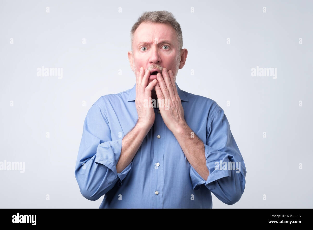 Senior european man with scared and anxious expression, bites finger nails - Stock Image