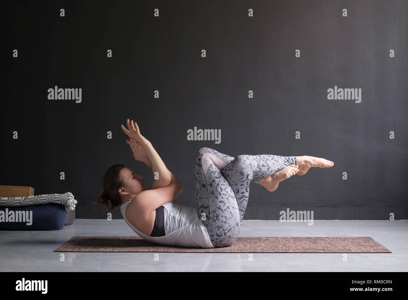 woman practicing yoga asana Ardha Navasana boat with garudasana variation - Stock Image