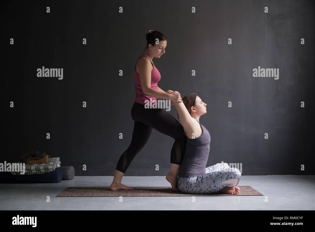 woman helping her friend to open shoulders and chest doing yoga asana, Stock Photo