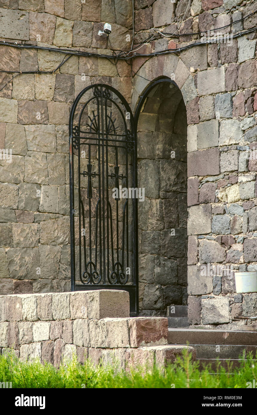 Stone staircase leading to arched doors with wrought-iron openwork door to exit from the courtyard of Geghard monastery in Armenia - Stock Image
