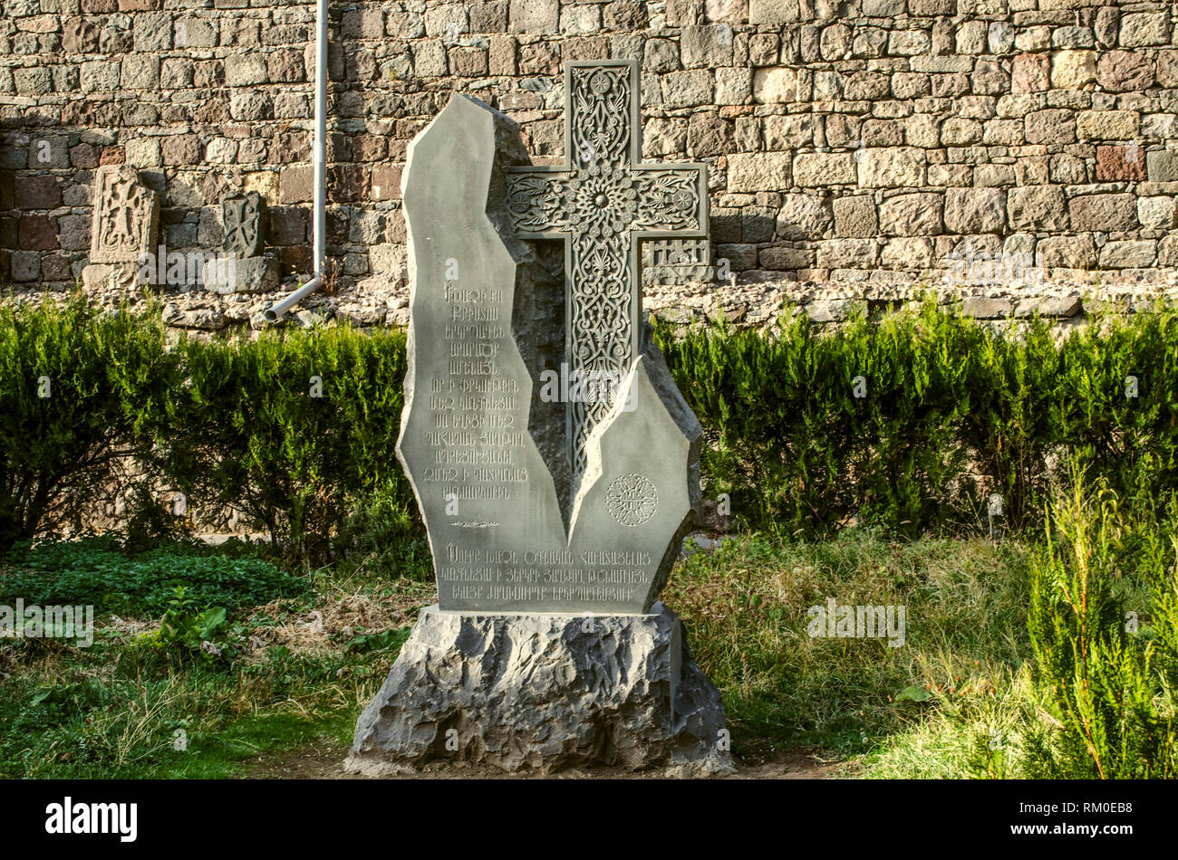 Geghard, Armenia, October 20, 2018:Khachkar from basalt carved as a donative to the monastery and installed in the Park near the stone wall, located a - Stock Image