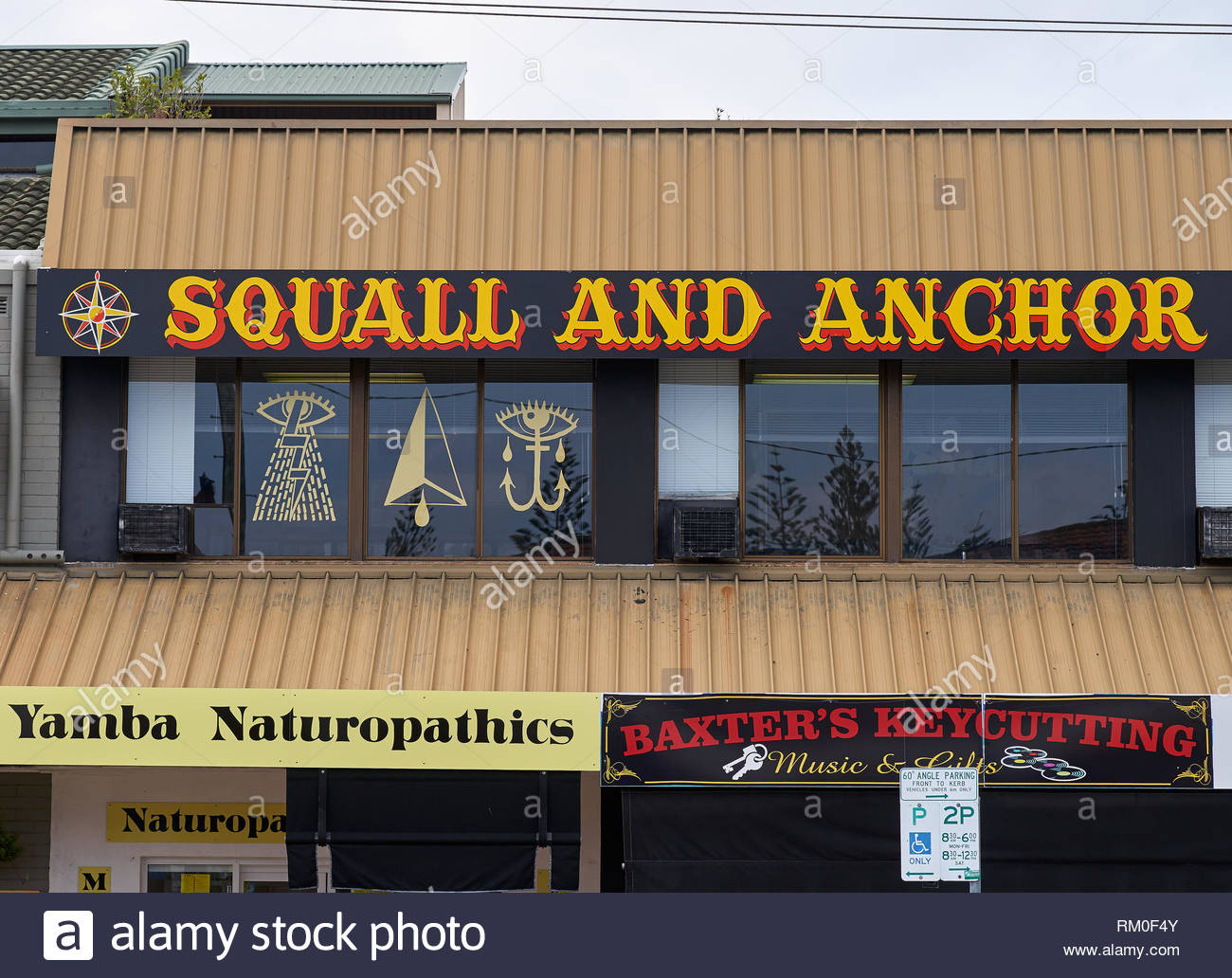 Shop frontage in the main street of Yamba - 'Squall and Anchor Tattooing', 'Yamba Naturopathics' and 'Baxter's Keycutting' - with satanic symbolism. - Stock Image