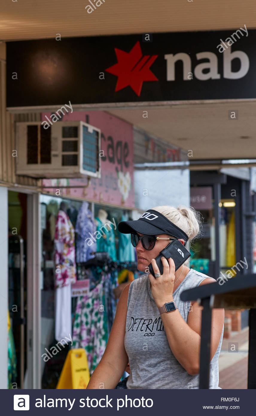A woman wearing a singlet, glasses, iwatch and sun-visor; talks on her smartphone as she walks past the shops and a bank, on the main street of Yamba. - Stock Image