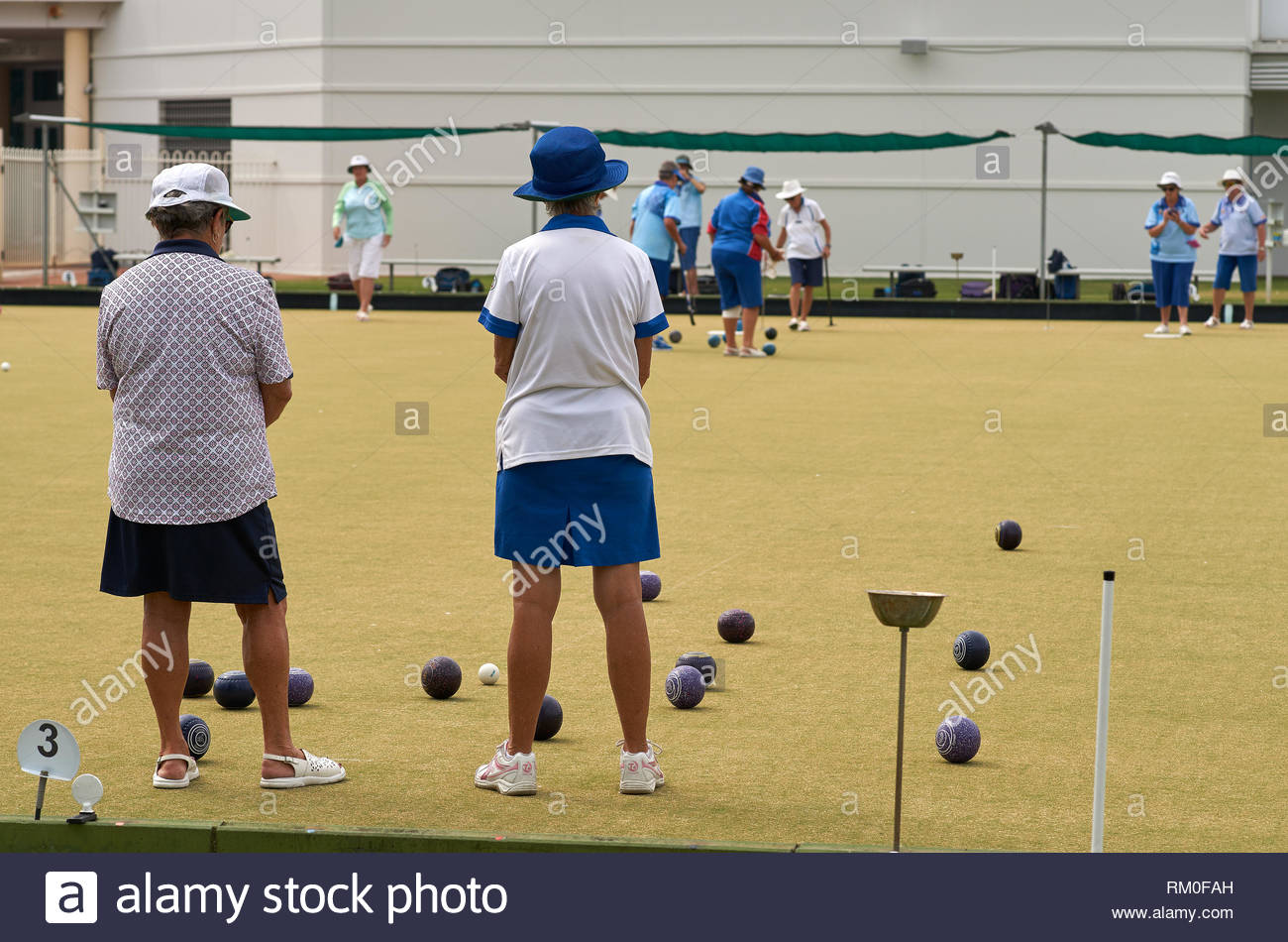 Older women in shorts, skirts and hats; playing amateur competition lawn bowls, at Yamba Bowls Club, during the summer of 2019. - Stock Image