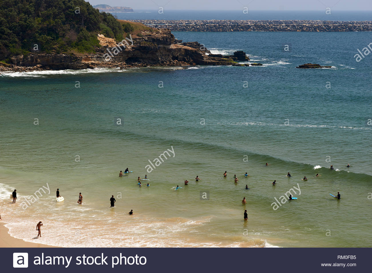 Lots of people cooling off - swimming in the sea, at Yamba Main Beach - during a  hot day of the Australian summer in 2019; at Yamba, NSW, Australia. - Stock Image