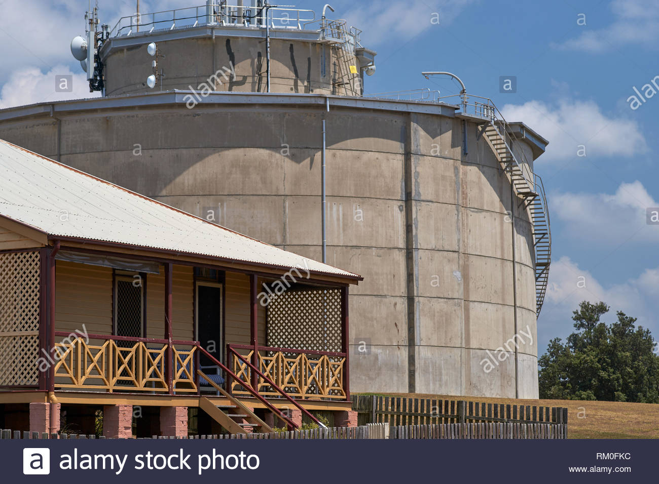The historic Boatman's Cottages; situated on Pilot Hill - dwarfed by a large concrete water-reservoir - on the grassy headland; at Yamba, Australia. - Stock Image