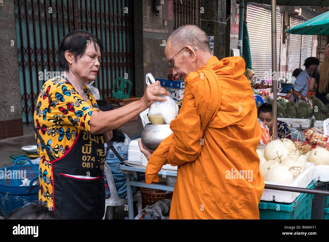 Alms giving at Nora street market, Hatyai, Thailand - Stock Image