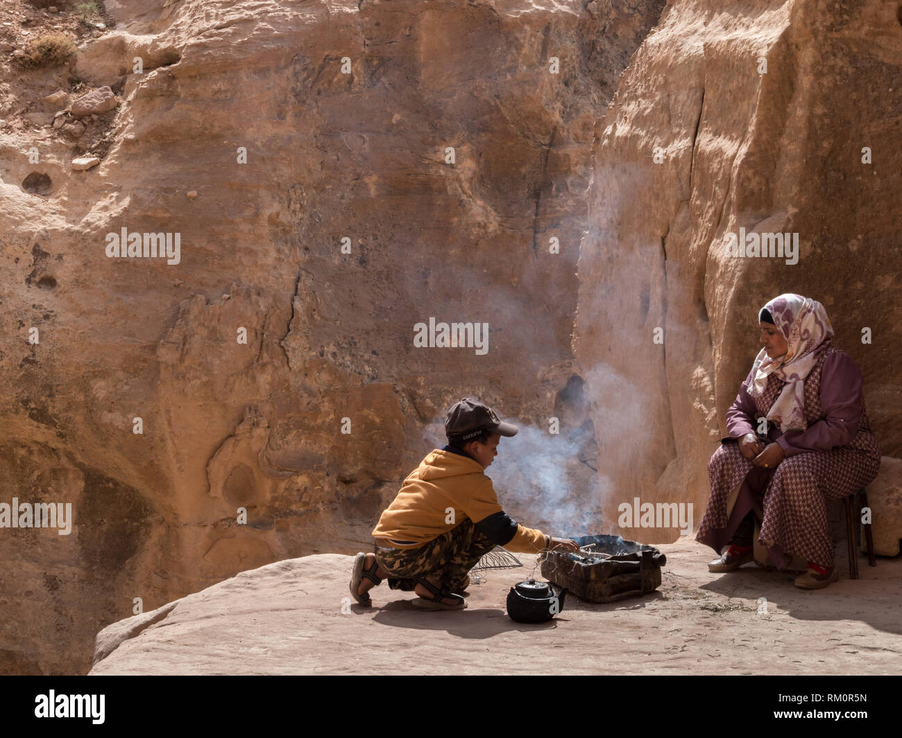 A young Bedouin boy carefully prepares a steaming hot meal and tea under the gaze of his mother at the base of a remote cave in Petra in Jordan. Stock Photo