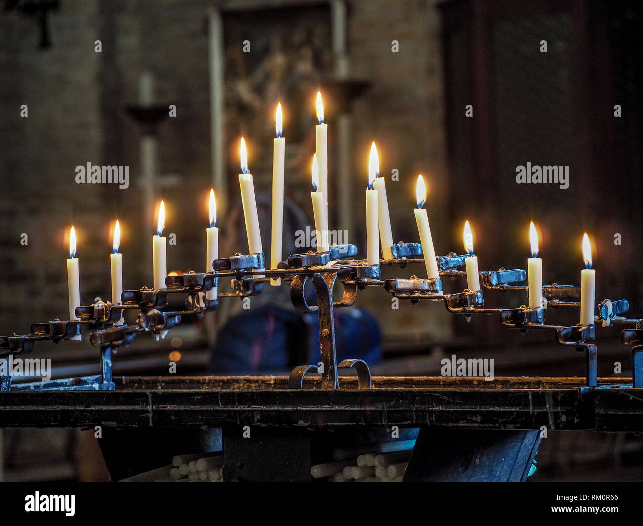 Candles glow warmly within the Cathedral of Santa Fosca on the Venetian island of Torcello. - Stock Image