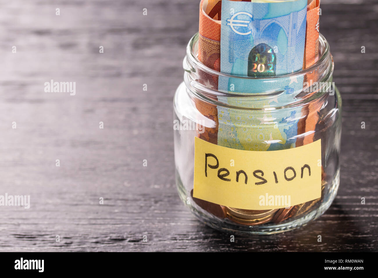 Glass jar with coins and euro notes on a black wooden table with an inscription PENSION. Concept of financial savings for wealthy old age Stock Photo