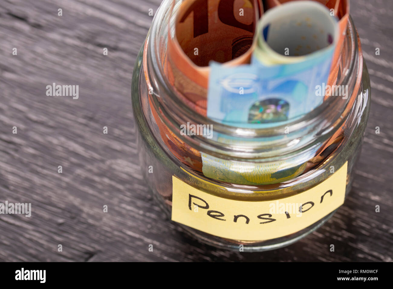 Glass jar with coins and euro notes on a black wooden table with an inscription PENSION. Concept of financial savings for wealthy old age - Stock Image