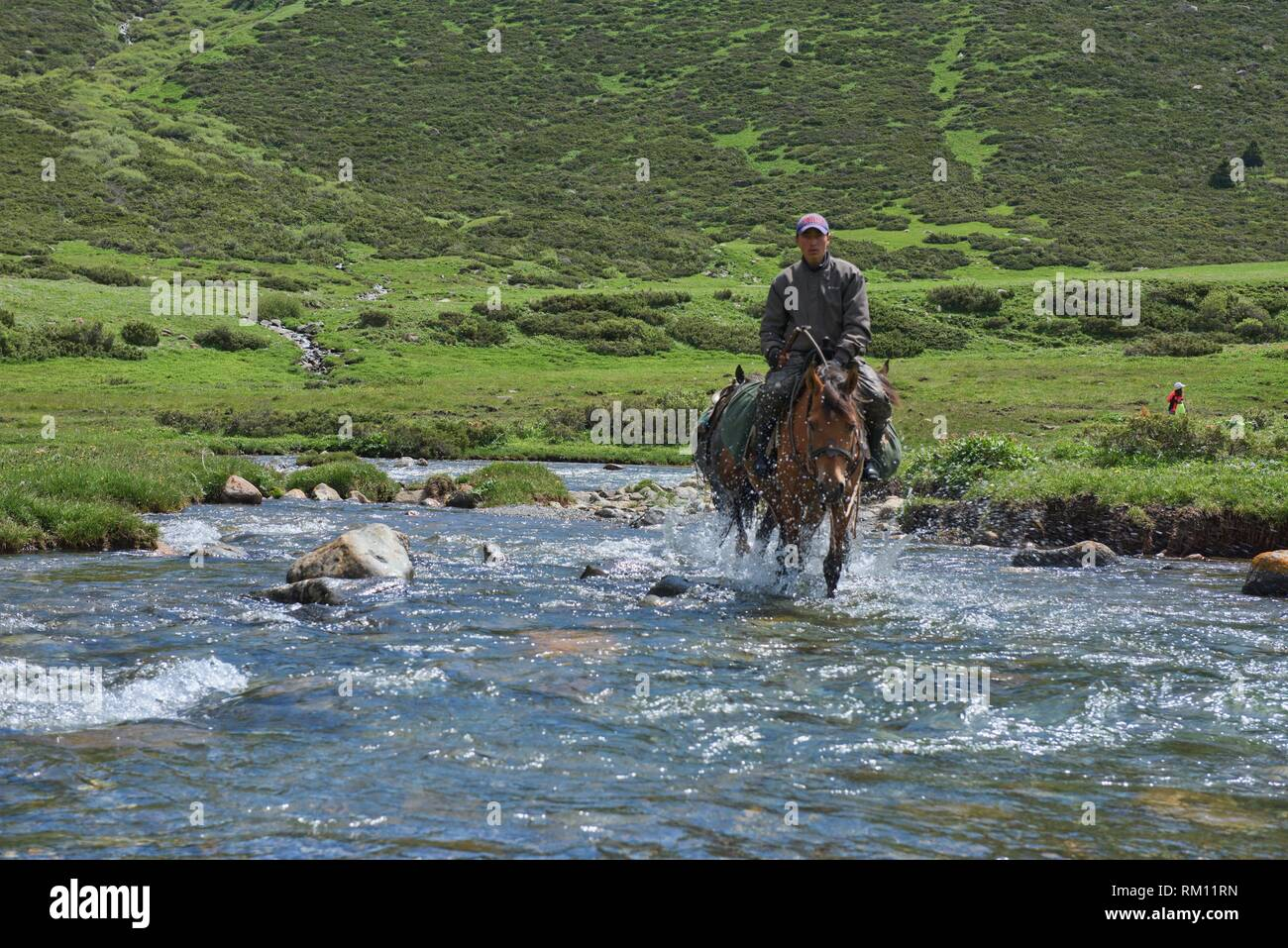 Kyrgyz horserider crossing the Tup River, Jyrgalan Valley, Kygyzstan. Stock Photo
