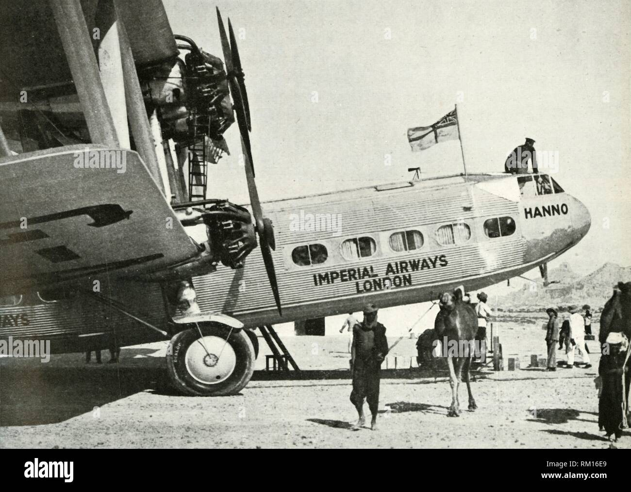 "Imperial Airways Handley-Page HP 42 biplane 'Hanno', Gwadar, Baluchistan, c1931-c1940 (1946). 'By 1929, Imperial Airways Ltd. had pushed their regular weekly service from Great Britain to India. The leisurely four-engined biplane 'Hanno' was typical of the land-based passenger aircraft of those days. She is at Gwadar, Baluchistan. From ""Merchant Airmen - The Air Ministry Account of British Civil Aviation, 1939-1944"". [His Majesty's Stationery Office, London, 1946]. Stock Photo"