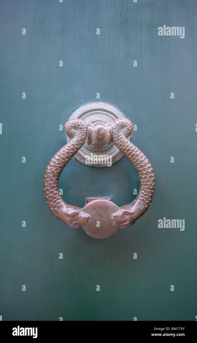 Architectural details - Antique bronze door knocker with snakes - Stock Image
