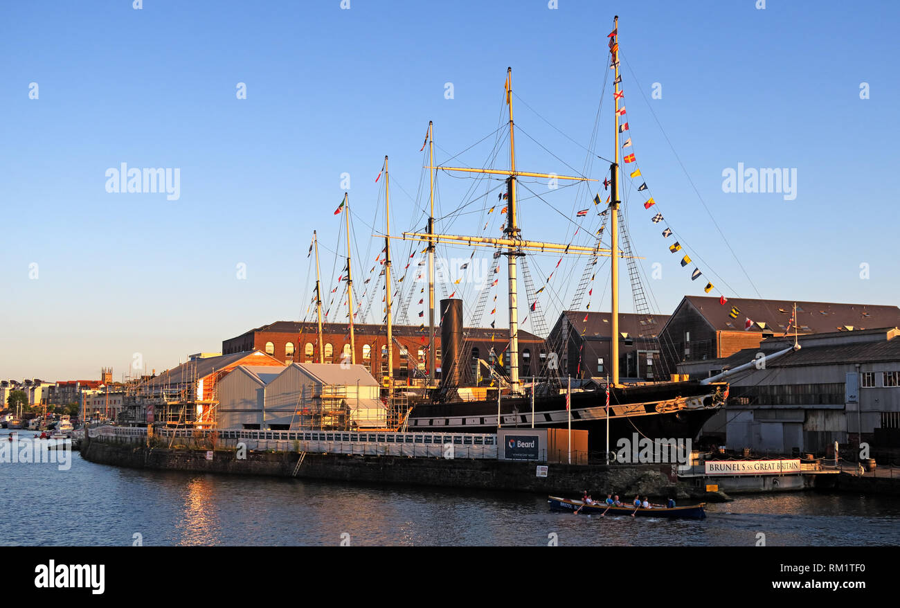 Rowers passing the SS Great Britain, Bristol Docks, South West England at sunset in the evening. - Stock Image