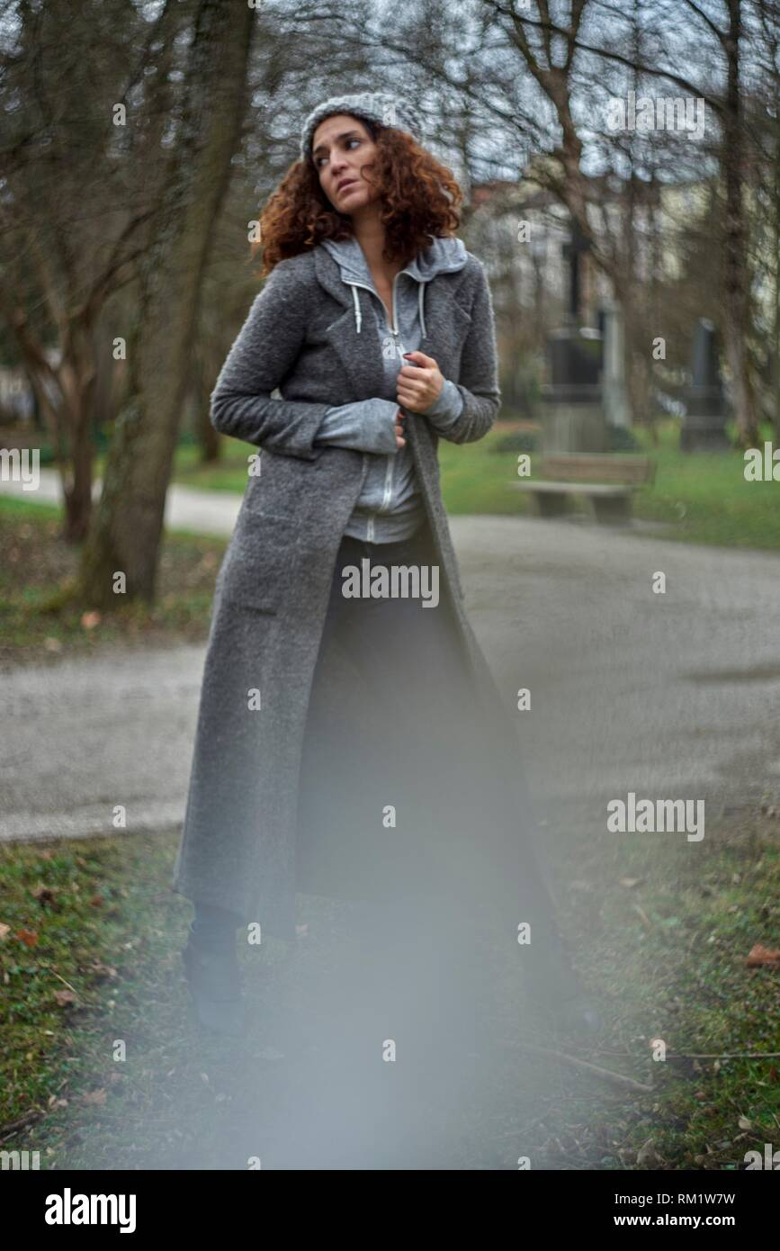 longing mature woman in winter clothes in park. Half German and half Turkish ethnicity. In Munich, Germany - Stock Image