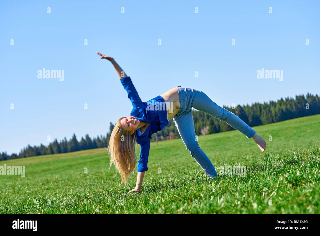 Woman turning a cartwheel on meadow, at countryside. Waakirchen, Bavaria, Germany. - Stock Image
