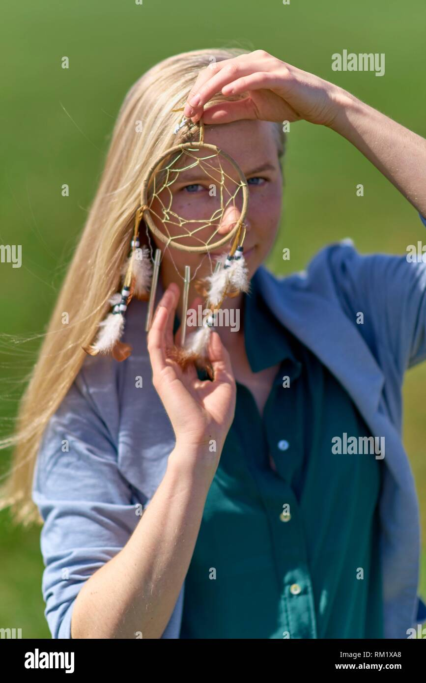 Waakirchen, Bavaria, Germany, woman behind dreamcatcher at countryside - Stock Image