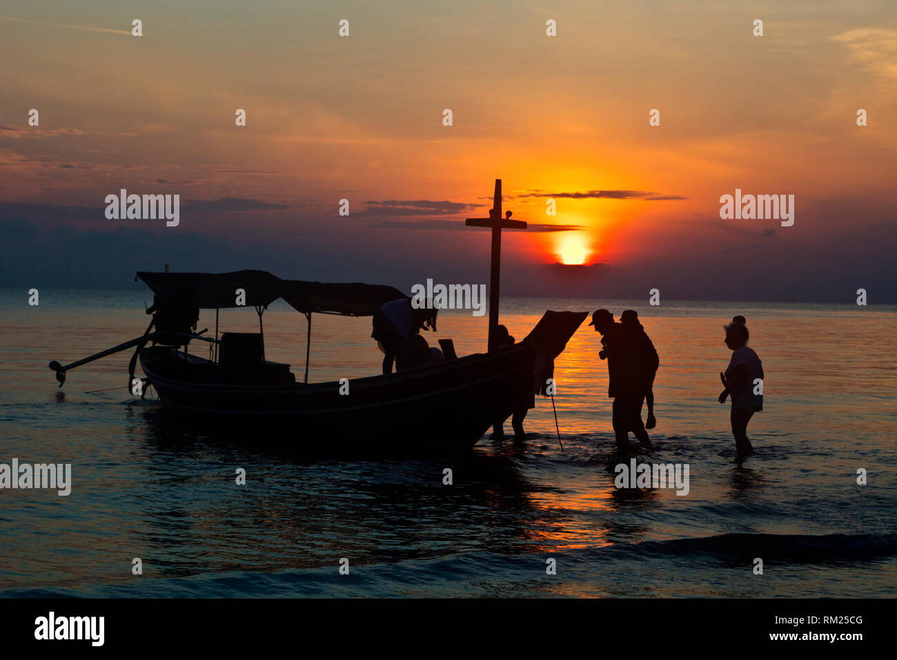 Getting on a longboat at sunrise on the beach of KHANOM, THAILAND - Stock Image