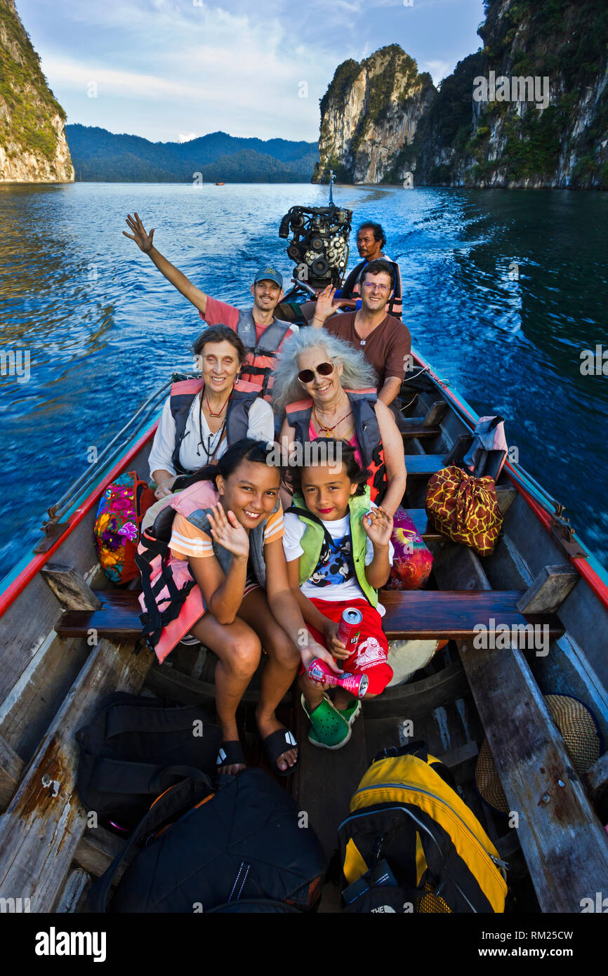 A tour on a long boat below KARST FORMATIONS rising out of CHEOW LAN LAKE in KHAO SOK NATIONAL PARK - THAILAND - Stock Image